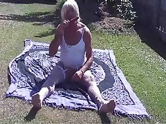 Blond crossdresser solo on the grass